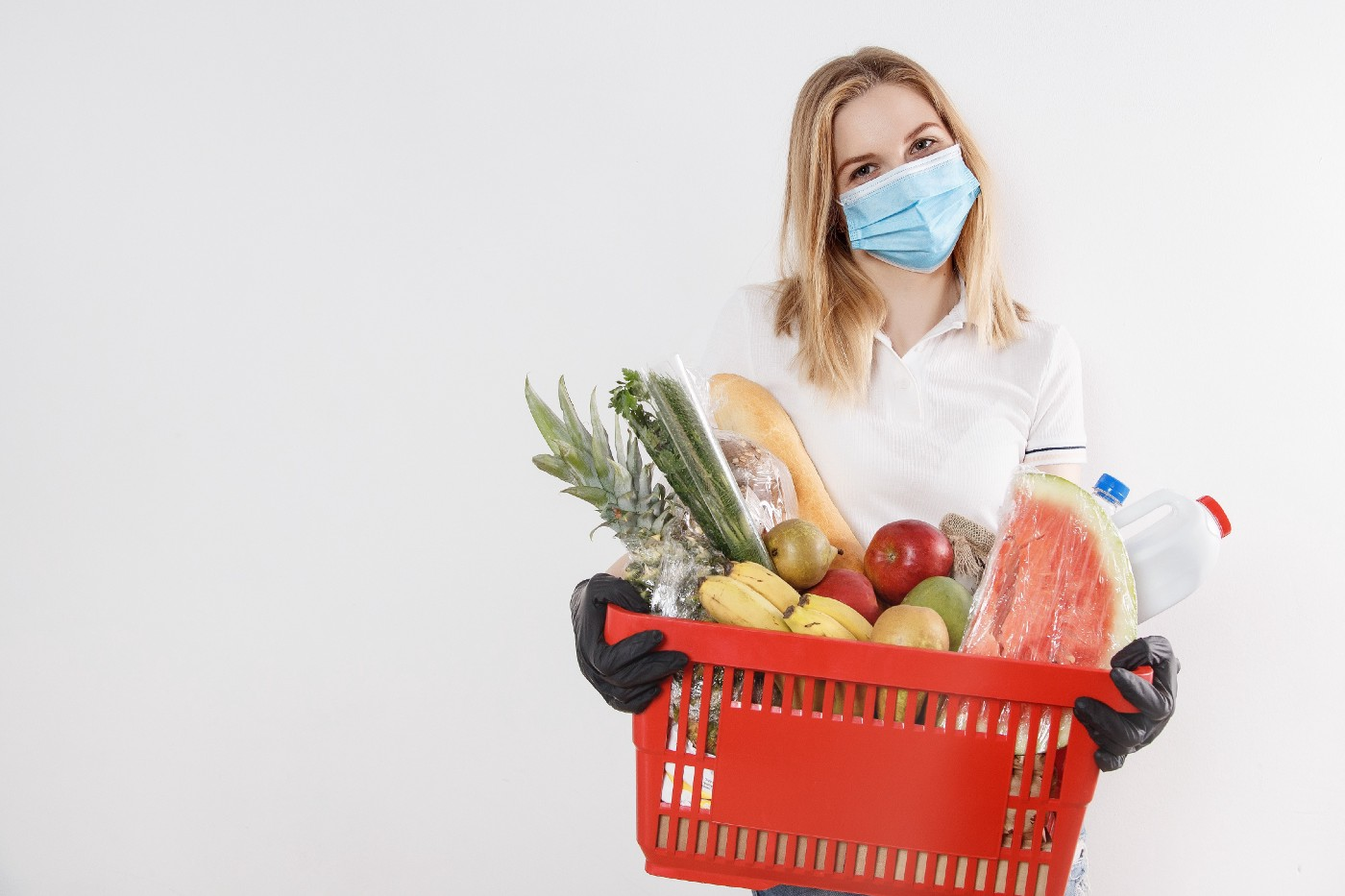 Woman wearing mask holding red basket of produce, including apples, watermelon, and pineapple.