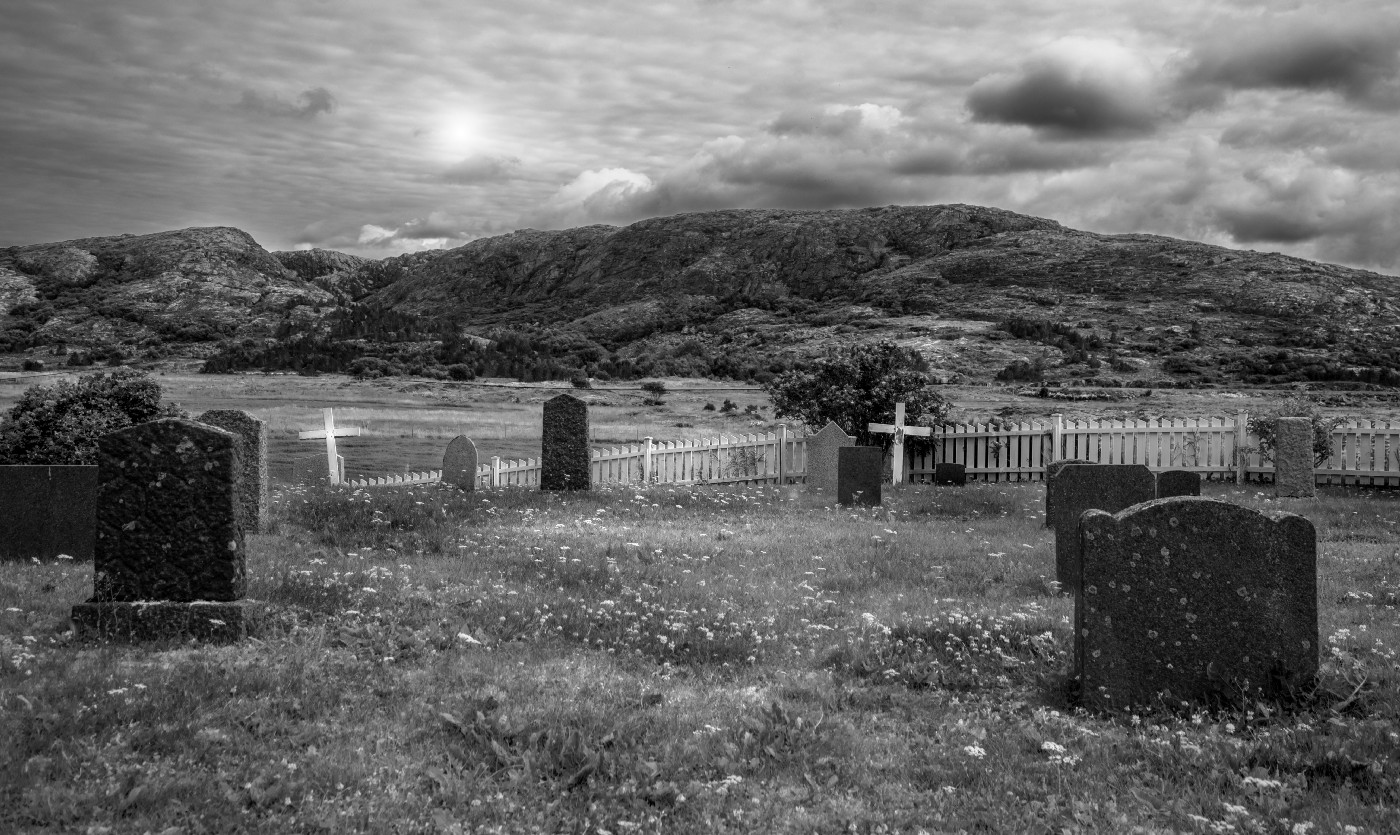A grey photo of a graveyard, with several graves in the front, a fence, and then a hill with the sun shining behind it.