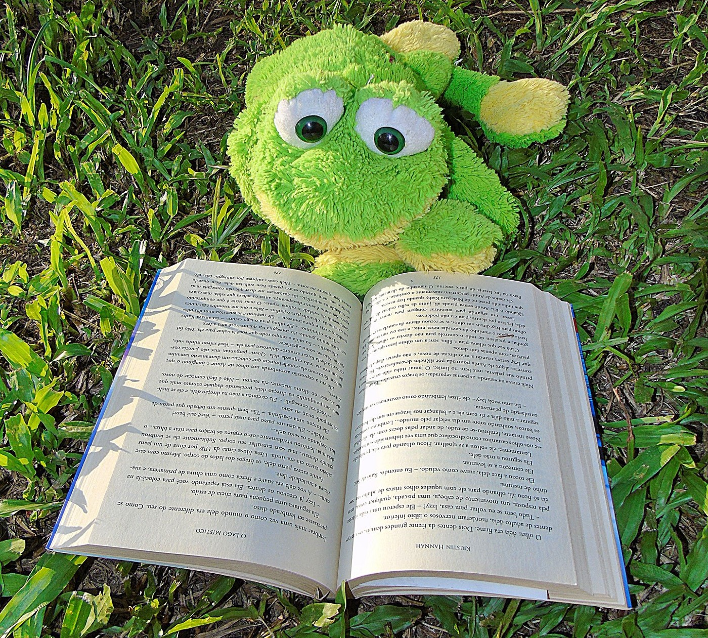 Green toy reading a book