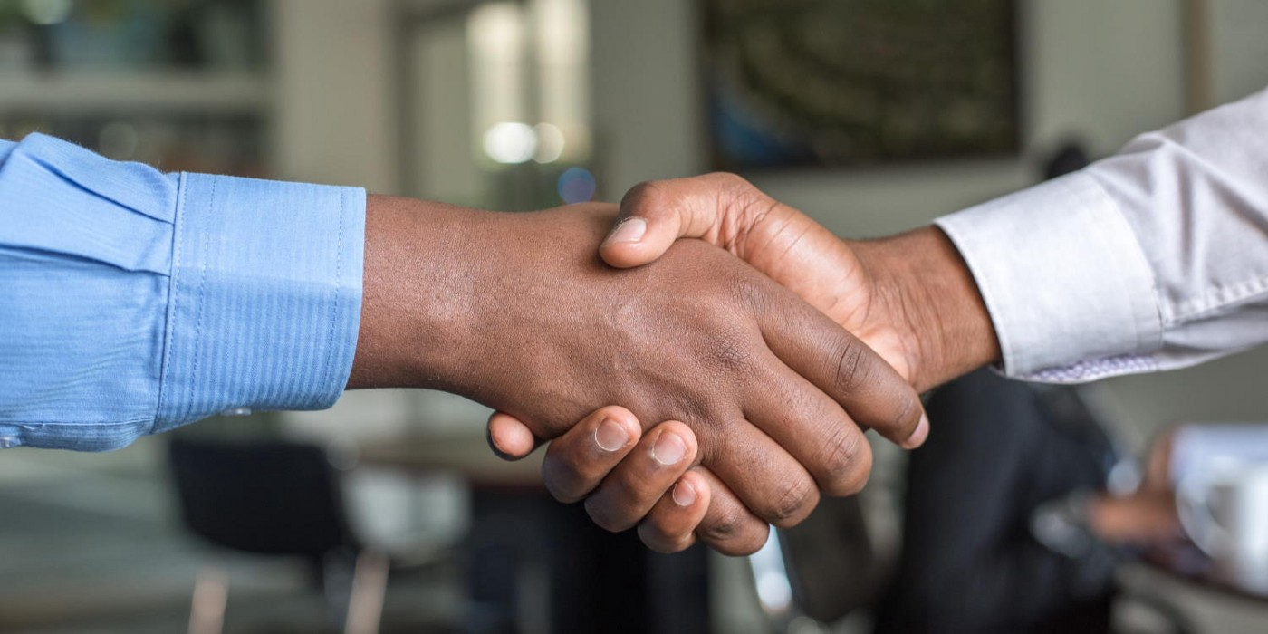 A closeup of two Black men's hands clasped in the most perfect of greetings in an office setting