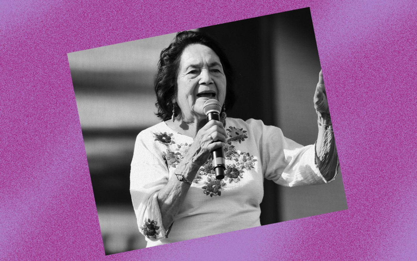 Black and white photo of Dolores Huerta against a violet background.