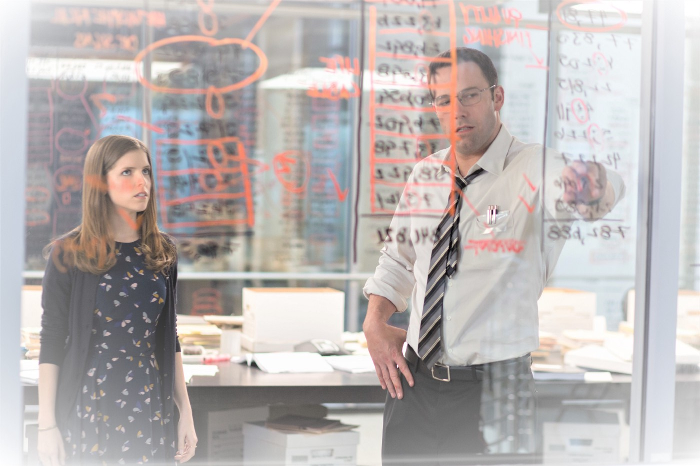 Scene from The Accountant. Ben Affleck is writing numbers on a glass window while Anna Kendrick watches.