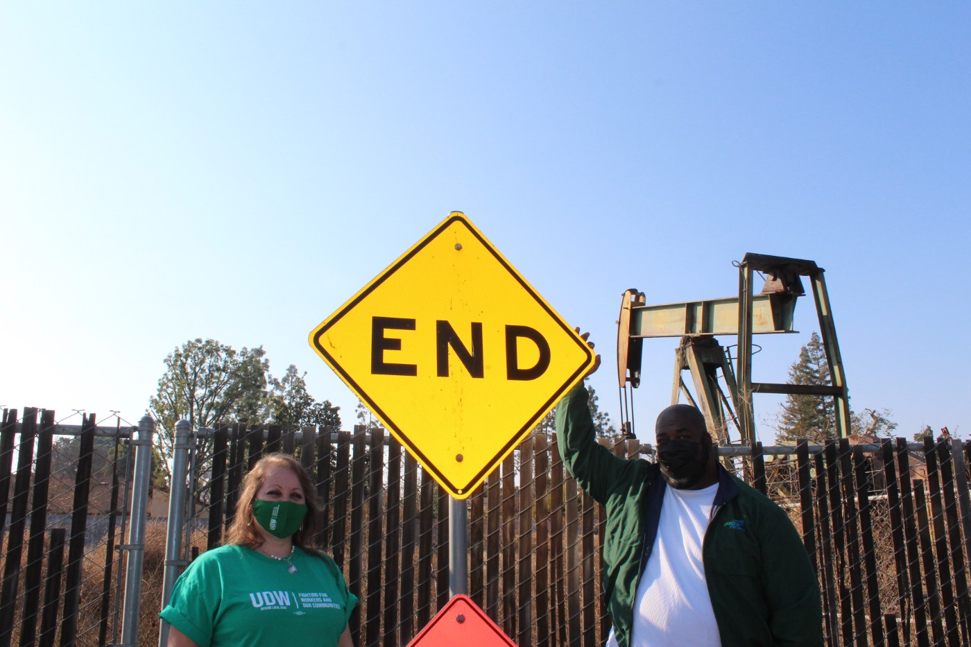 "Two union members stand in front of an oil pump and a bright-yellow sign that says ""END."""