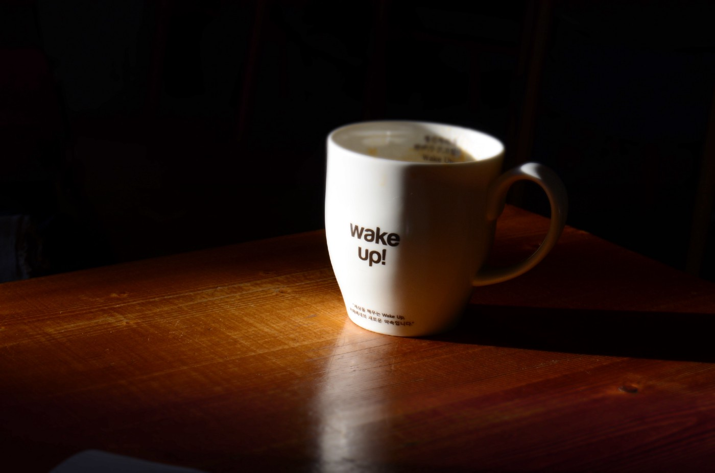 White coffee mug with Wake Up written on it.