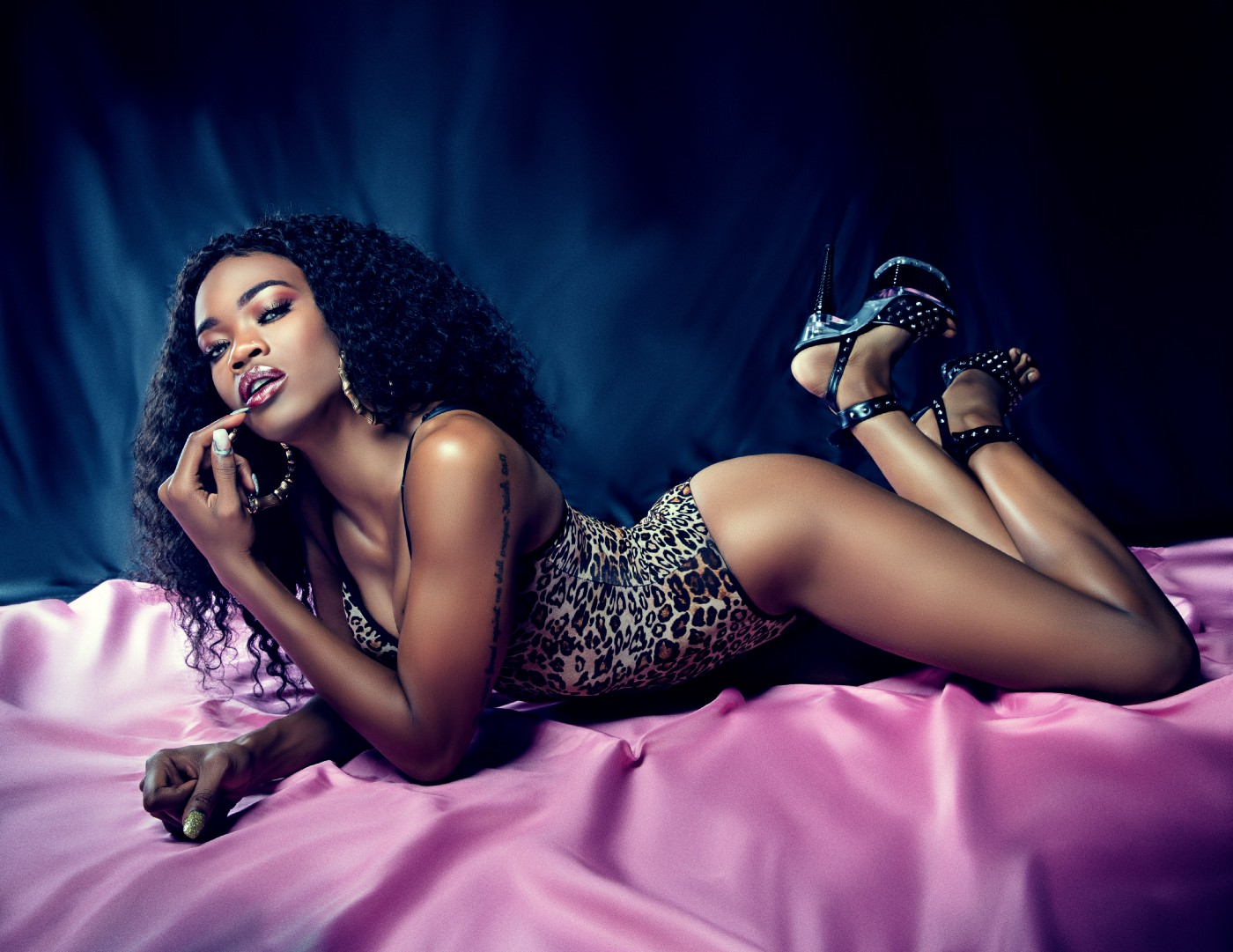 Black woman in sexy pose on her stomach, finger to her lip. Wearing a leopard print leotard style body suit and leopard print high heels. Long, curly black hair. Sultry makeup.