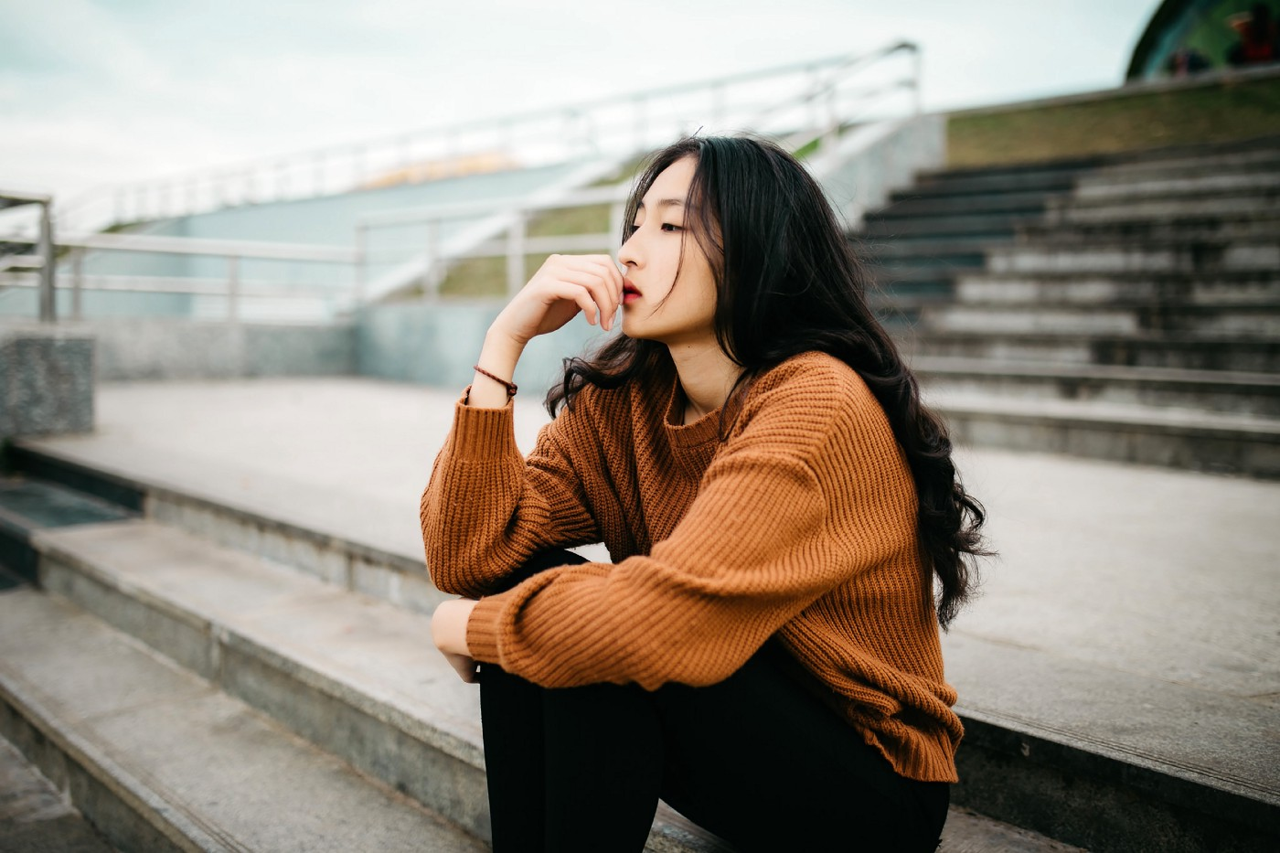 Women sitting on stadium steps with a chestnut sweatshirt and black jeans deep in thought.