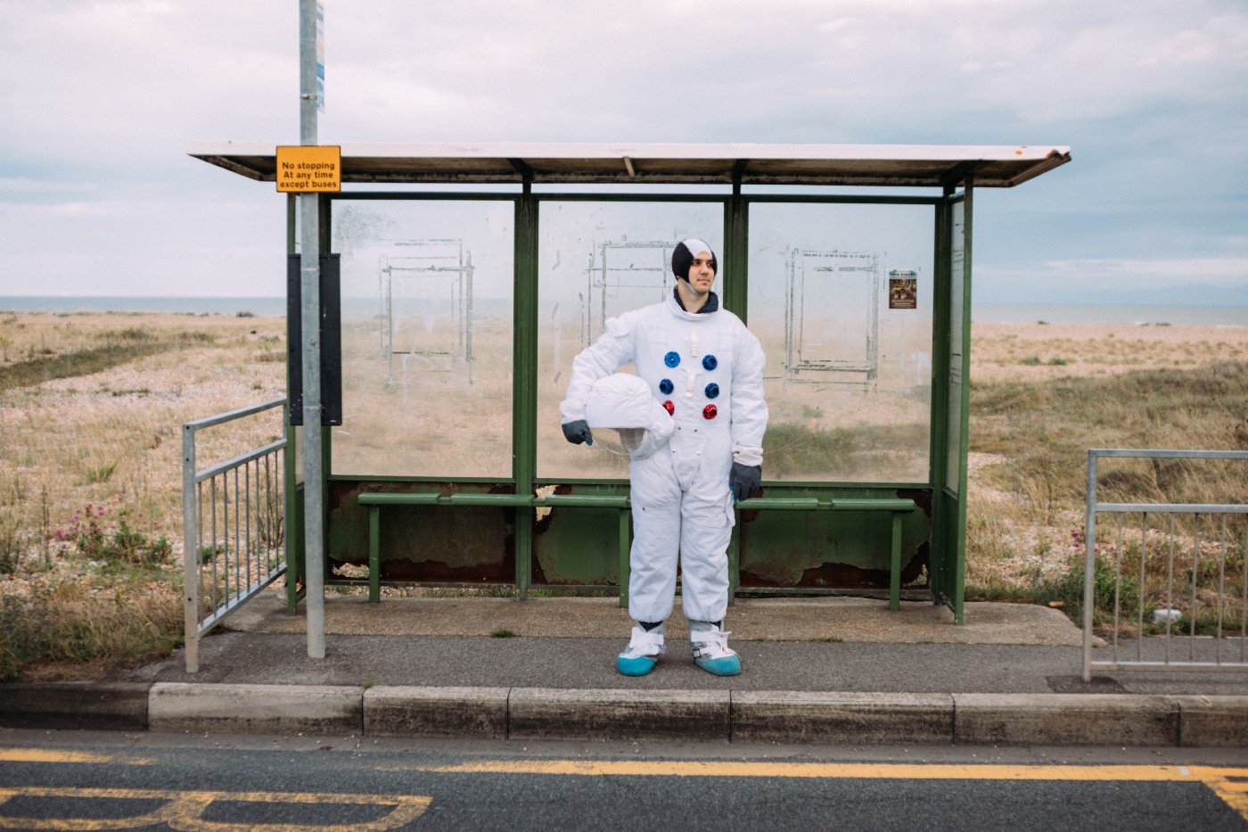 Man in an astronaut suit waiting at a bus stop.
