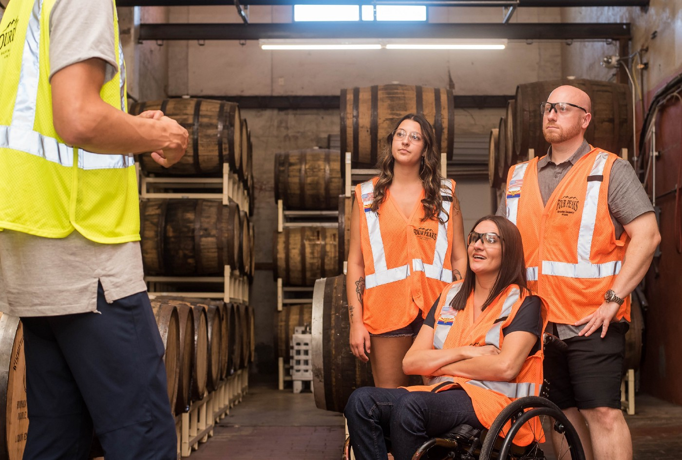 Four individuals in a warehouse setting wearing brightly colored safety vests, one of them a woman in a wheelchair