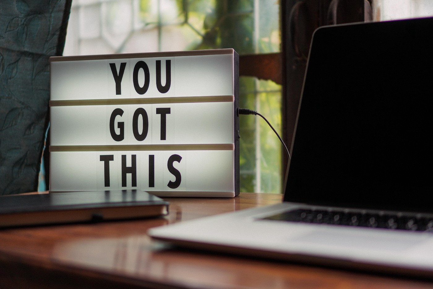 """A laptop sitting on a desk with a sign beside it stating """"You Got This"""""""