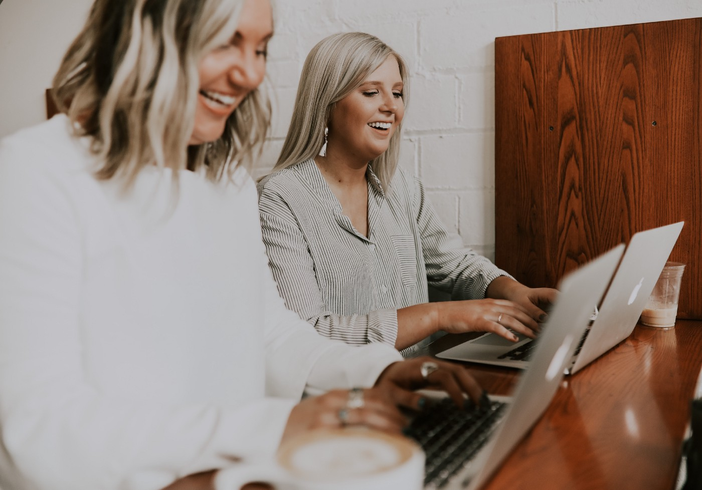 Two women blog at a desk with coffee.