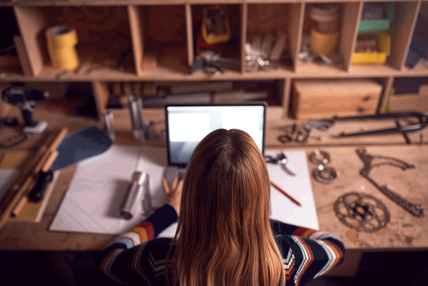 young business owner working late in workshop on her side hustle