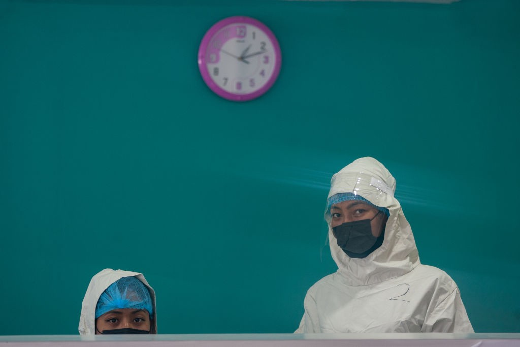 A photo of two healthcare workers wearing masks standing at a counter against a teal background.