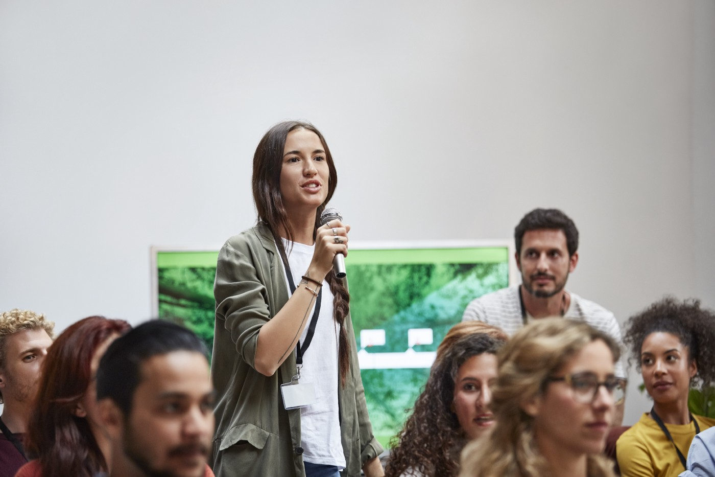 A woman speaks into a microphone, asking questions while standing amidst colleagues.