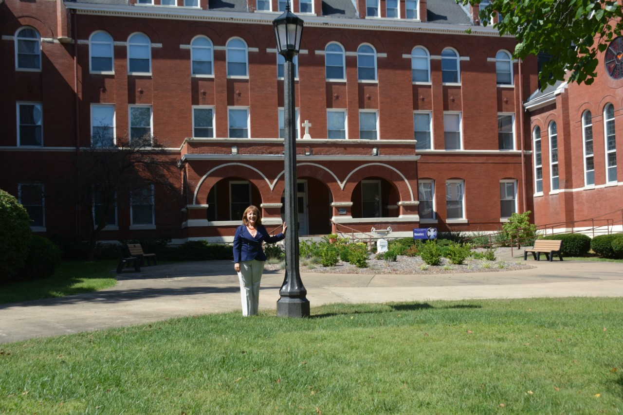 Photo of author Judith Valente beside lamp post in front of red brick arched entryways of Mount St. Scholastica Monastery.