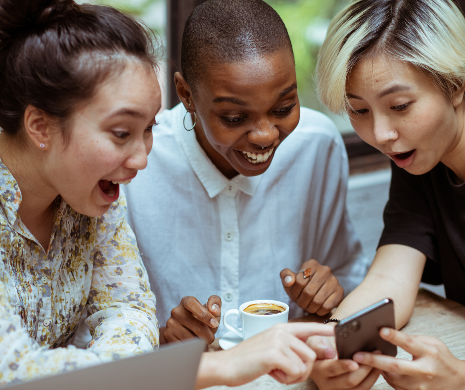 Fun group of three women looking surprised and excited by what they see on a phone