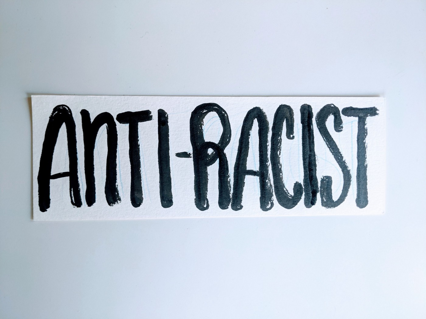 """Hand lettering of """"Anti-racist"""" in all capitalized letters painted in black ink on white strip of paper."""