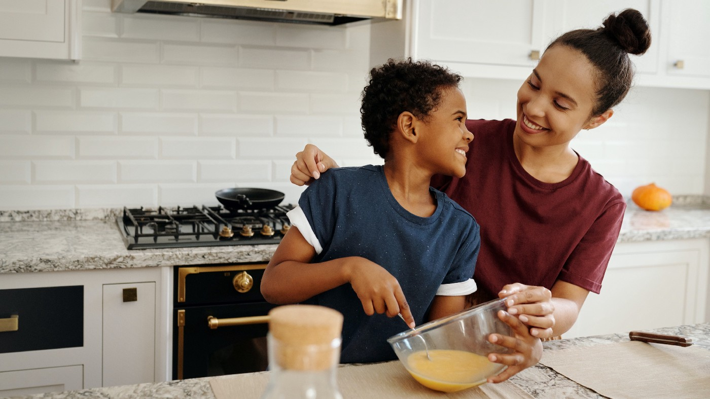 A mother and son stand at a kitchen counter stirring batter together.