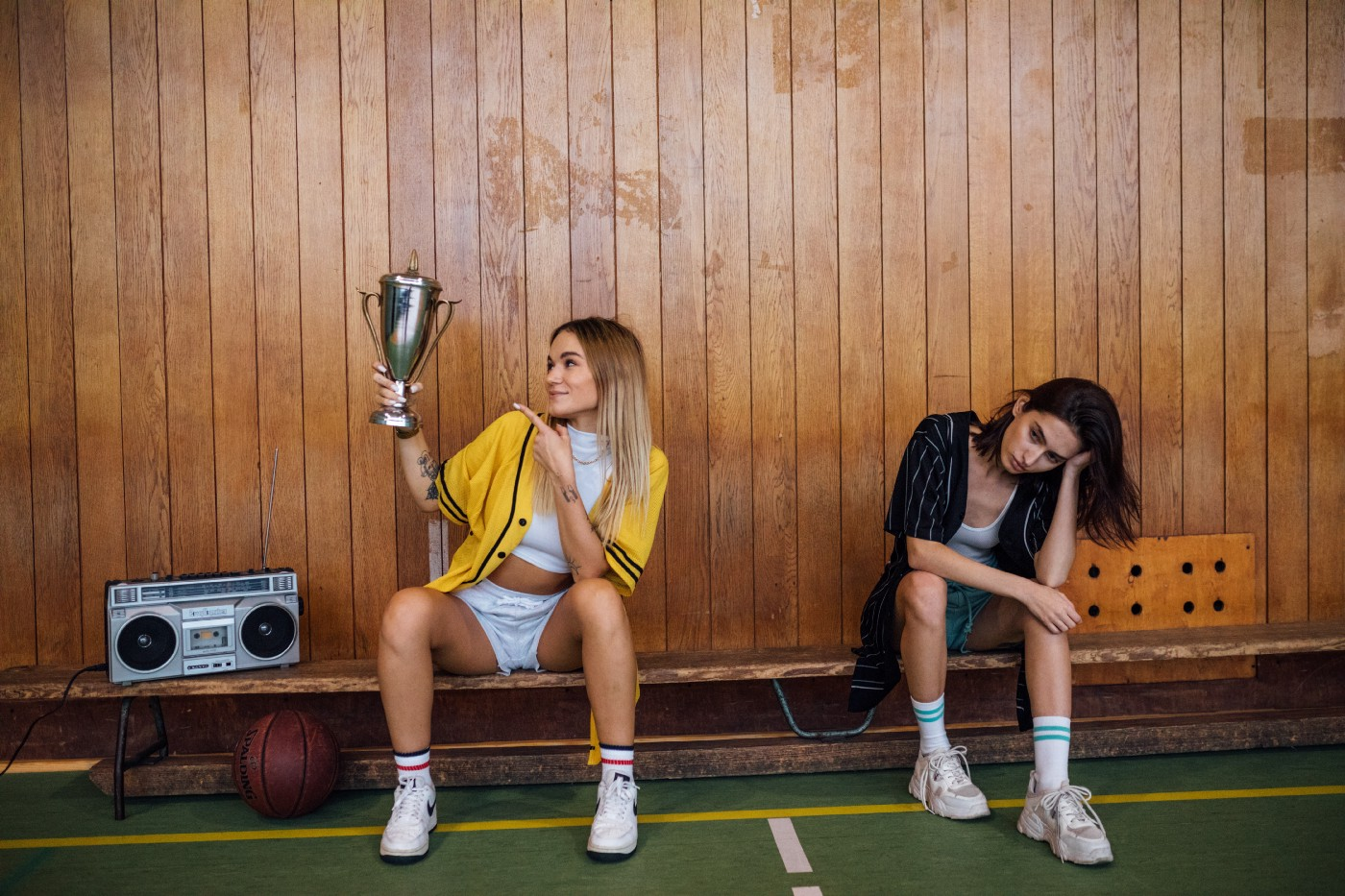 Two girls sitting on a bench after a game. One holding a trophy and one sad that she lost.