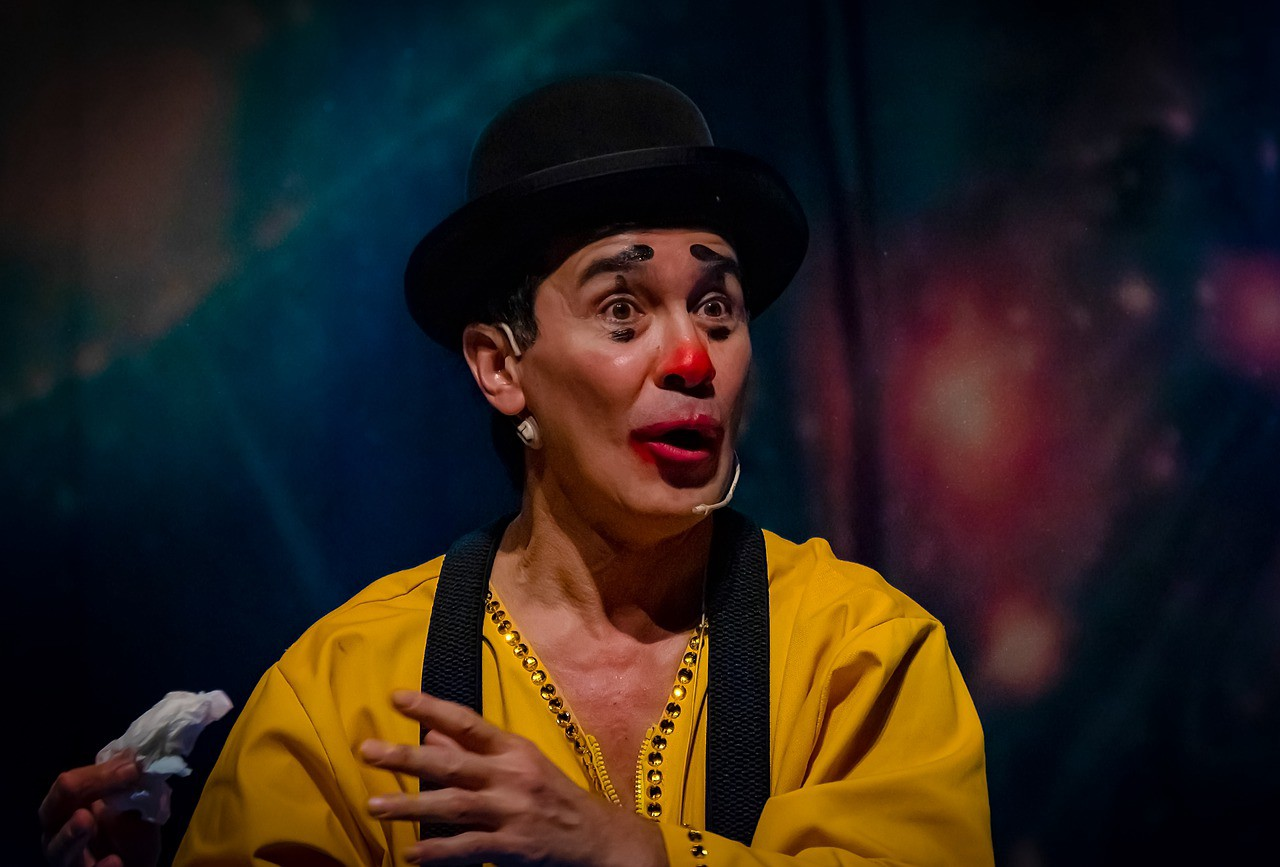 A circus clown with a bowler hat is telling a story
