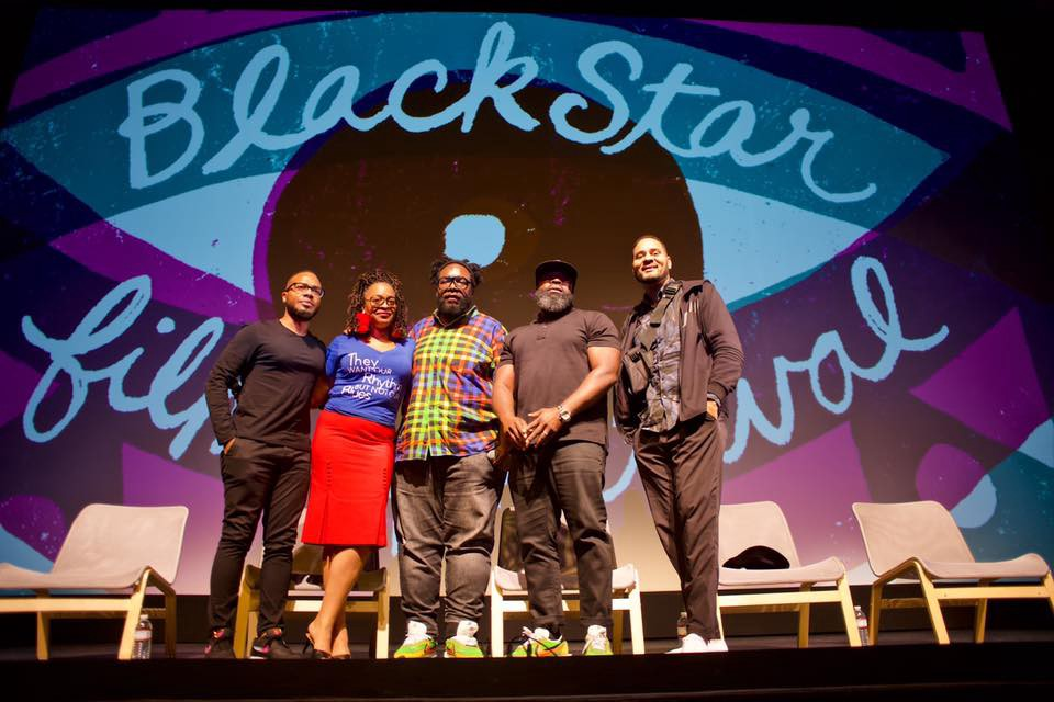 Panelists at the Black Star Film Festival pose for a photo on stage.