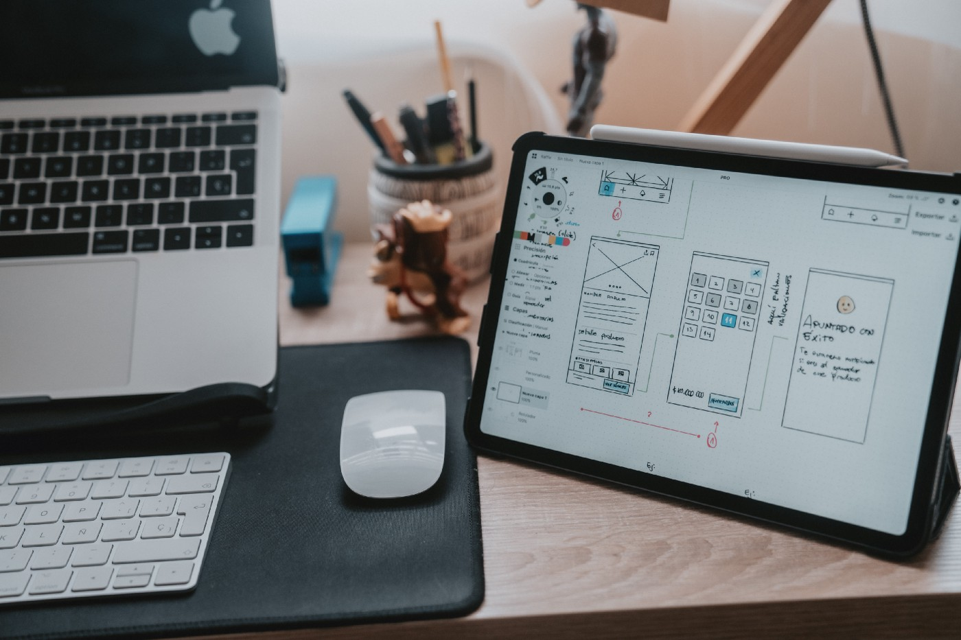 An image of a laptop and mouse sitting next to an ipad with sketches of UI screens filled with words.