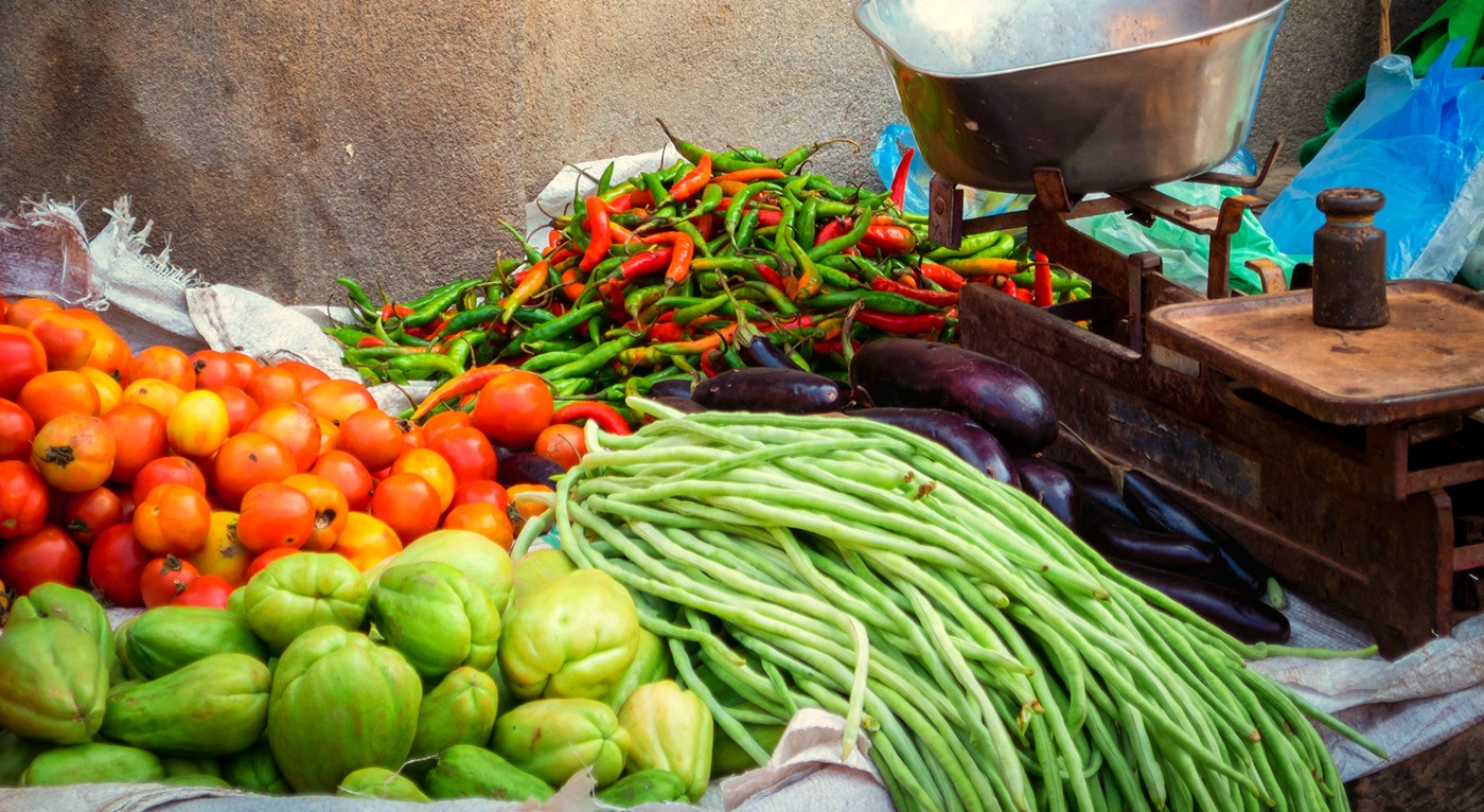 Tomatoes, peppers, cho cho and other organic food produce on a market vendor's stall.