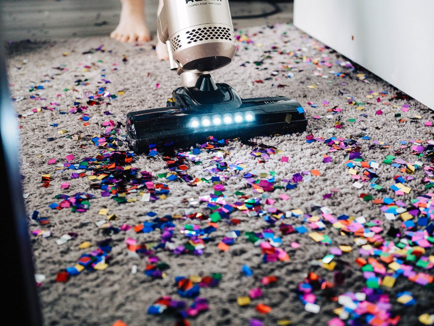A vacuum cleaner vacuuming confetti and other colorful bits off of a carpet