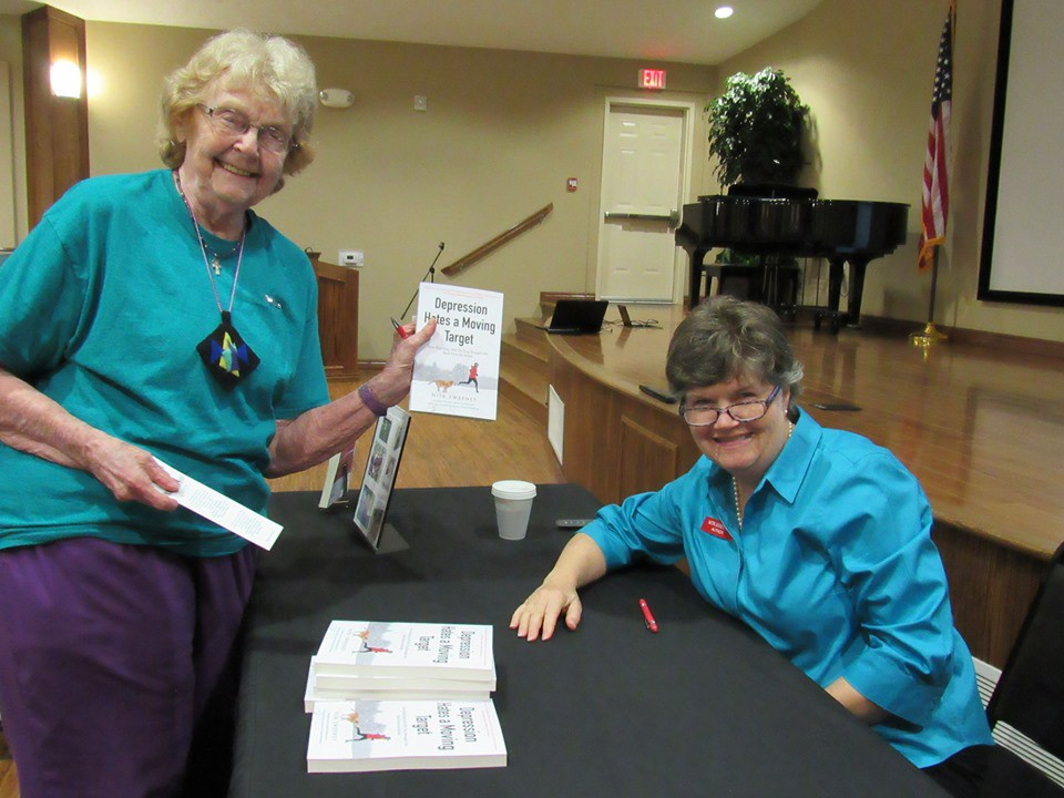 Woman holding book at author book signing.