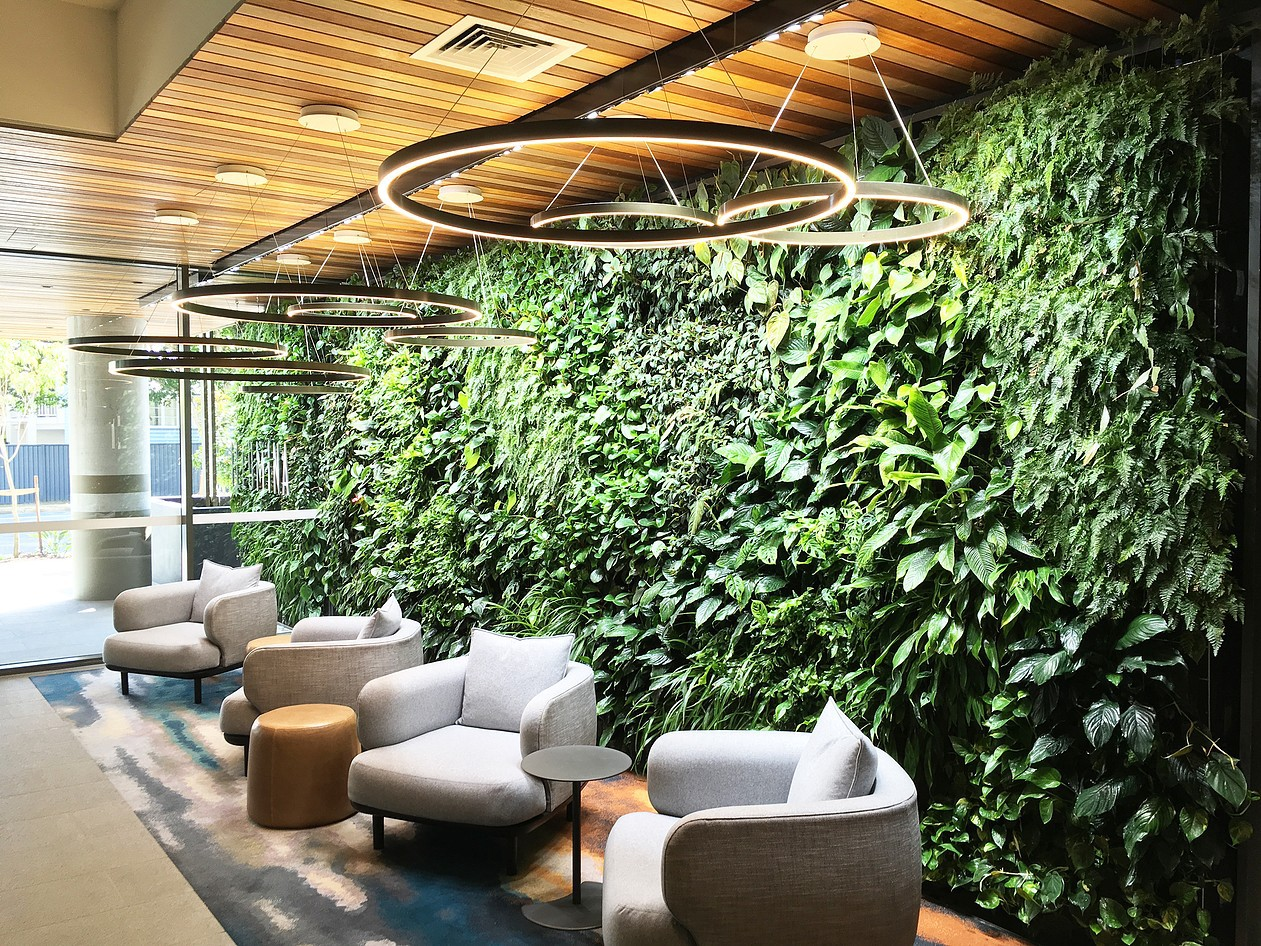 A variety of lush green plants covering a floor to celing wall. Infront are some chairs and tables.