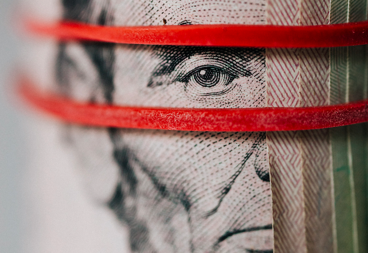 A roll of American dollars with two bright red elastics, framing Abraham Lincoln's face.