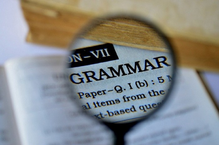 The word grammar in all caps as seen through a loupe, a small magnifying glass.