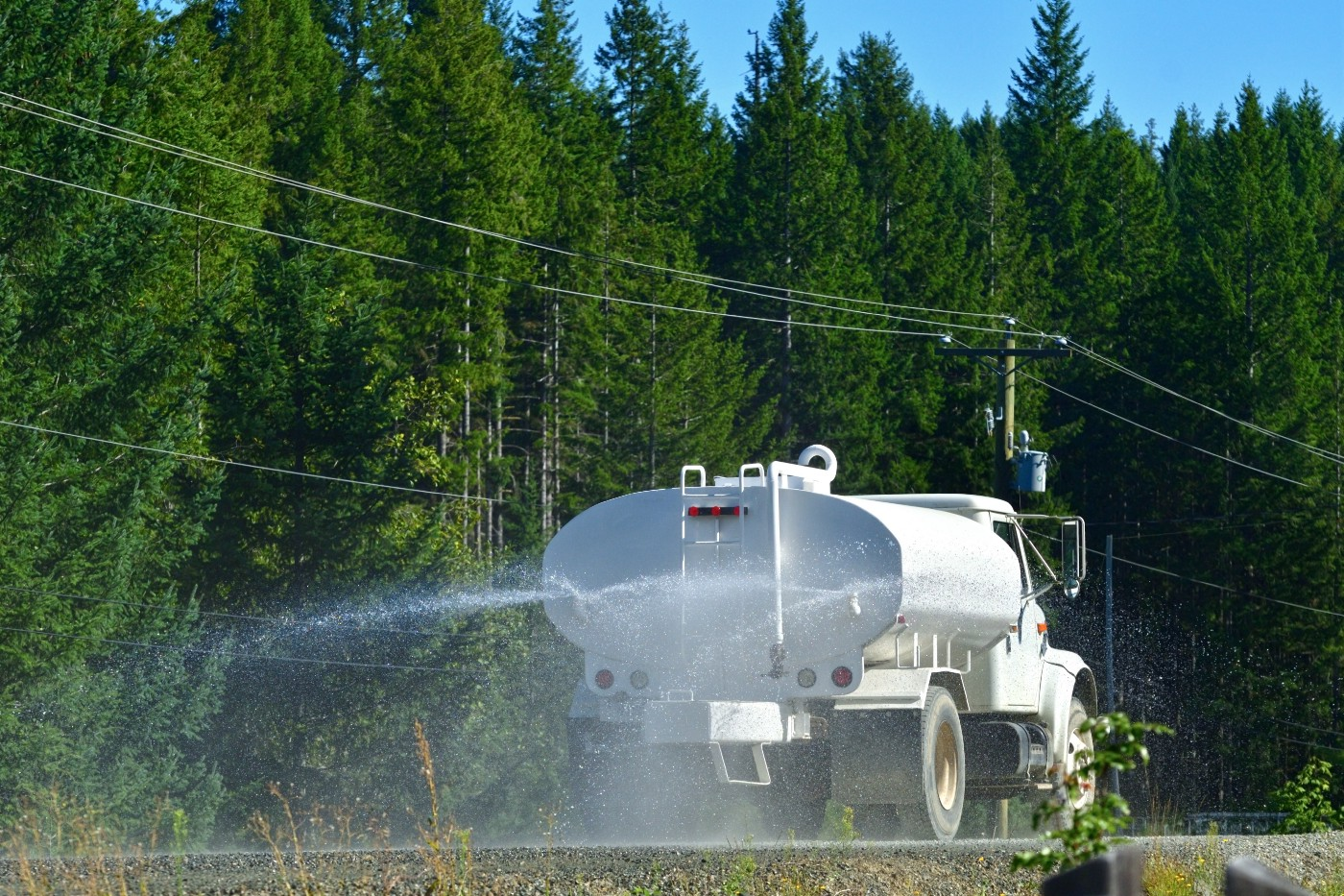 A dust suppression truck is traveling through a road surrounded by green trees while spraying water to suppress dust.