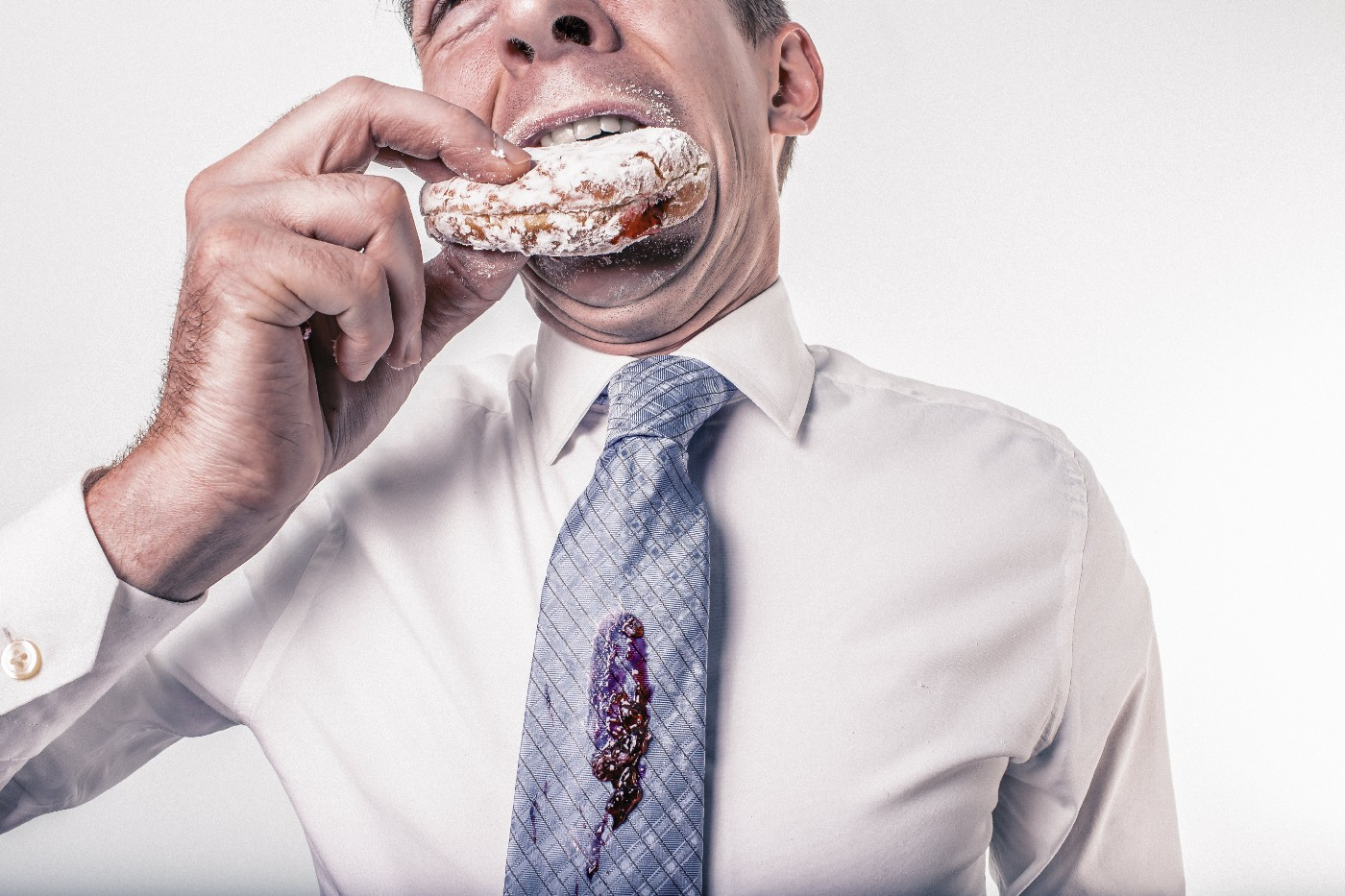A man in business casual clothing eating a jelly doughnut with jam on his tie.