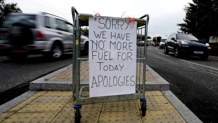 """A white sheet of card tied crudely to a metal trolley on a yellow pedestrian crossing that reads """"SORRY WE HAVE """"NO"""" MORE FUEL FOR TODAY APOLOGIES"""" written by hand in capital letters"""