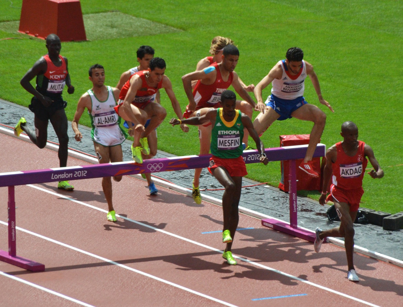Male runners in steeplechase heat jumping over a hurdle on a running track