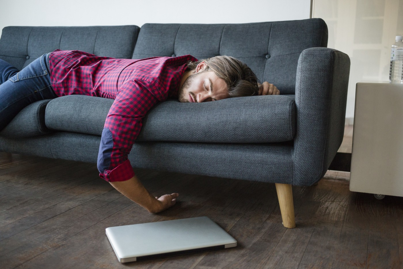 A photo of a sleeping man on the couch, laptop on the floor.