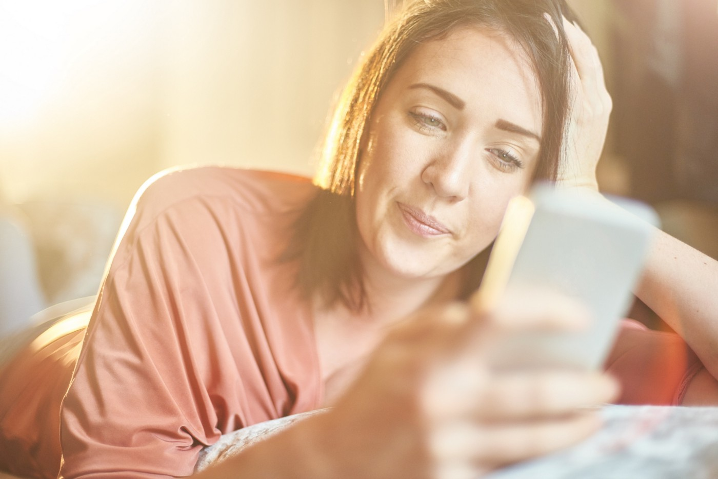 A young woman lying on a sofa looking through an online dating app.