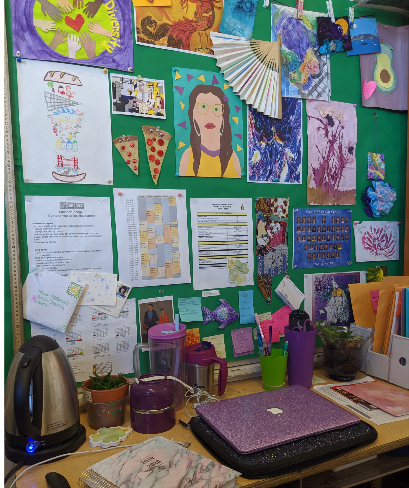 A teacher's desk with a bulletin board filled with art on wall behind.