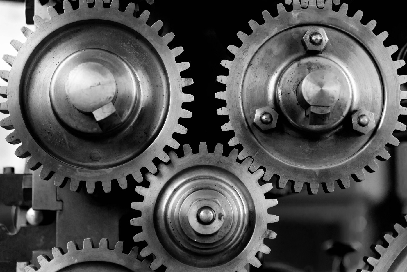 Picture of a small gear interlocked between two larger gears