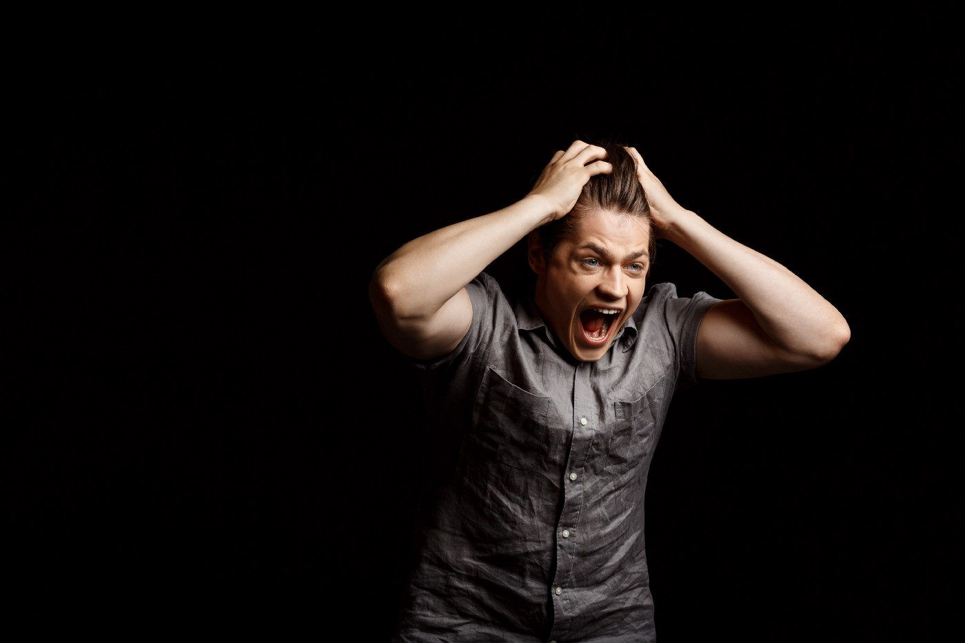 Man screaming against a black background