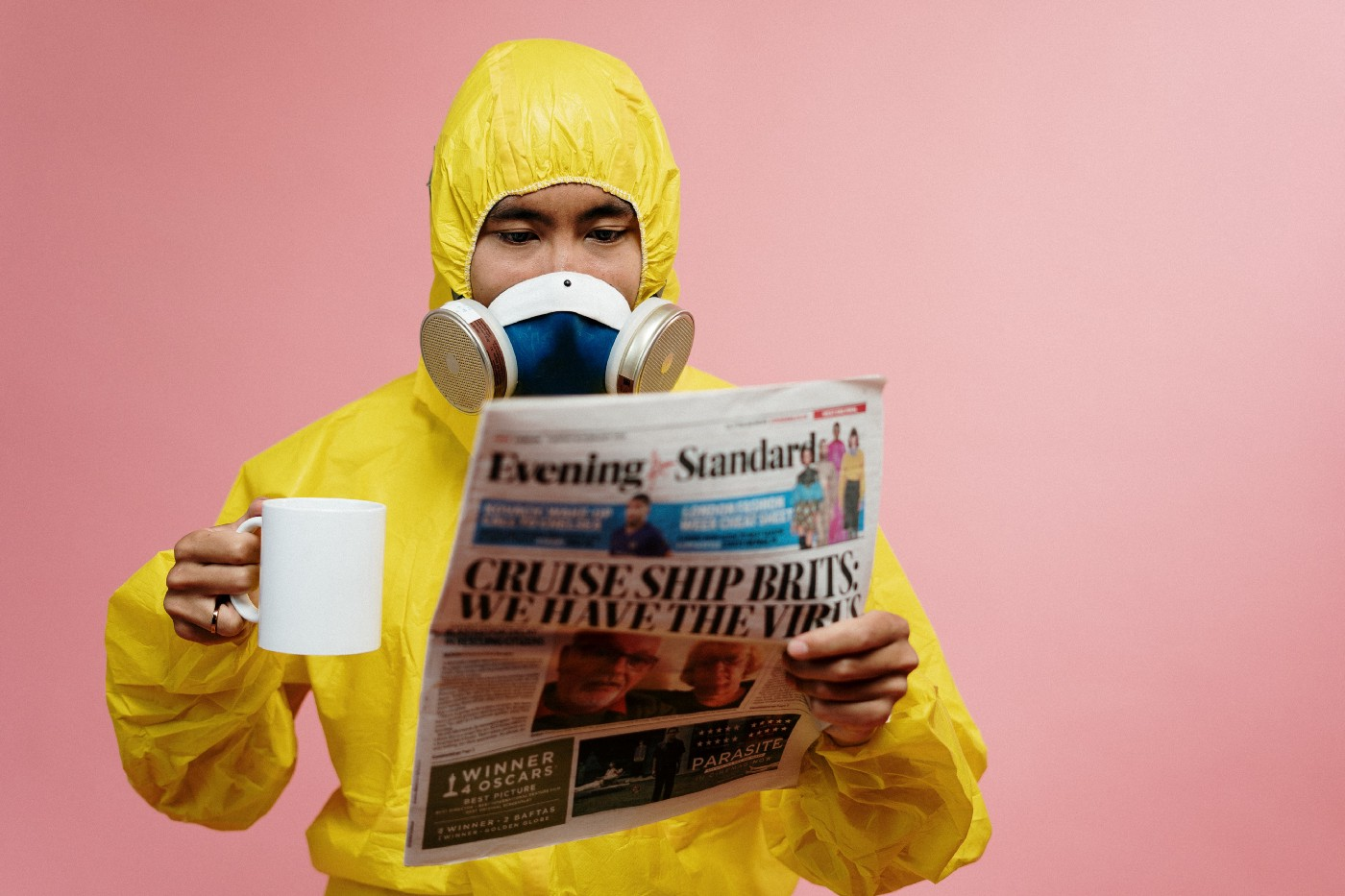 Dude in protective gear with coffee reads newspaper. For some reason the background is pink. It looks weird.