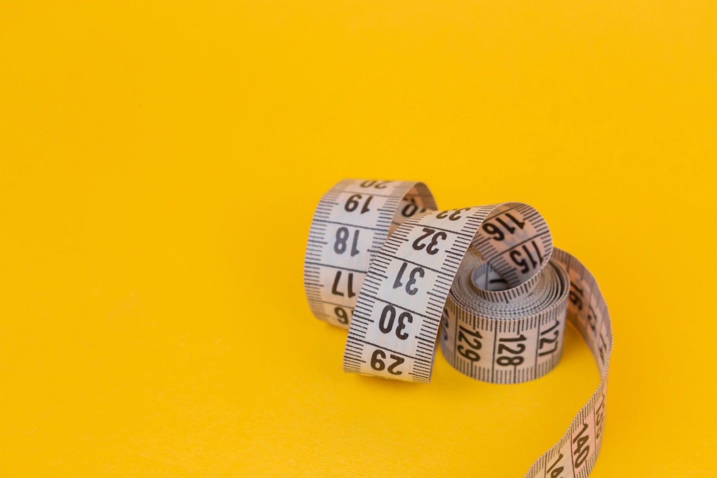 A coiled measuring tape rests against a solid yellow background