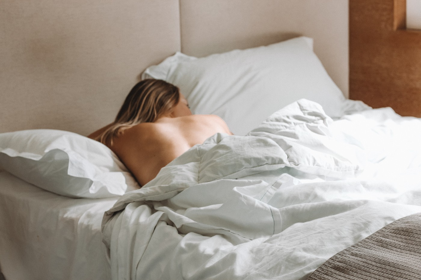 A bed with white linens with a long haired woman laying on her stomach sleeping. Sunlight streams in.
