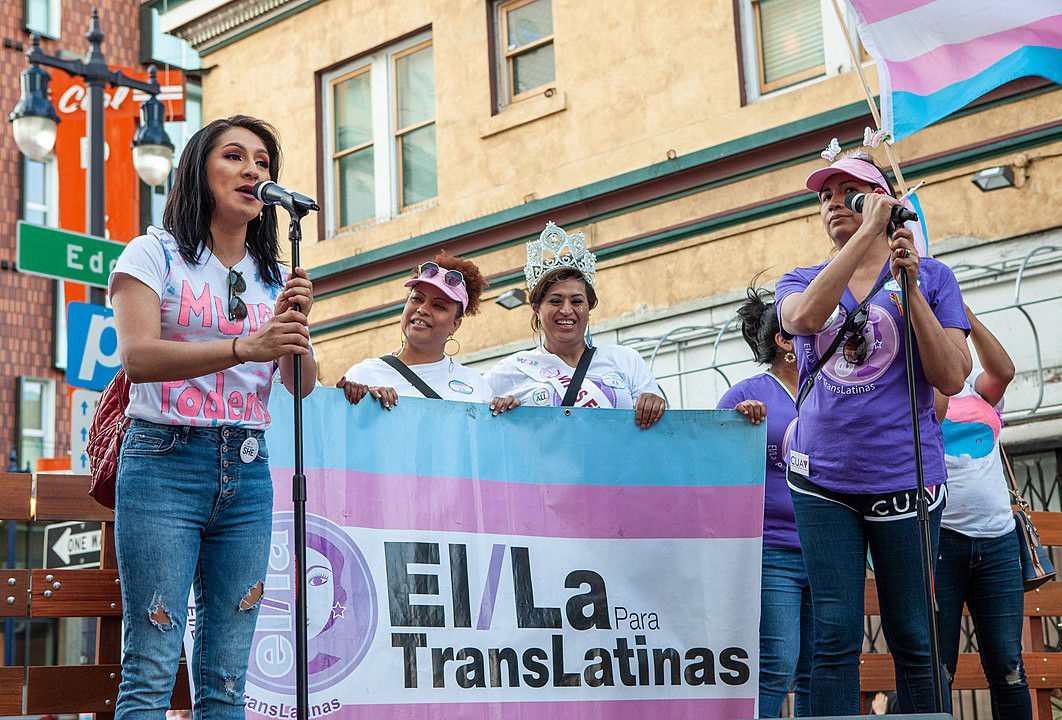 A group of trans Latinas stand on a stage. One speaks into a mic, one holds a trans flag, others hold a banner.