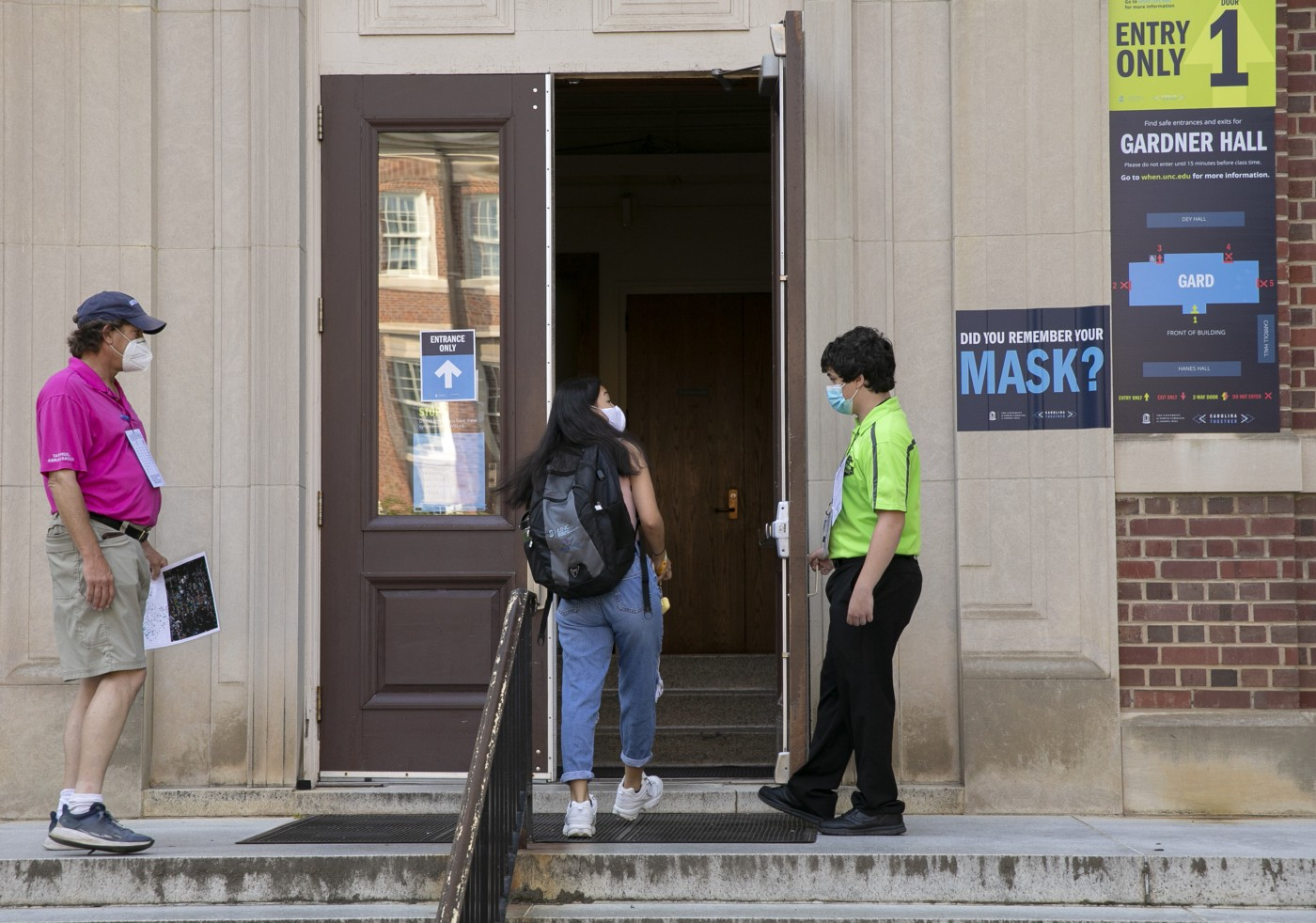 Safety ambassadors checking a student wearing a mask prior to entering a building at UNC-Chapel Hill.