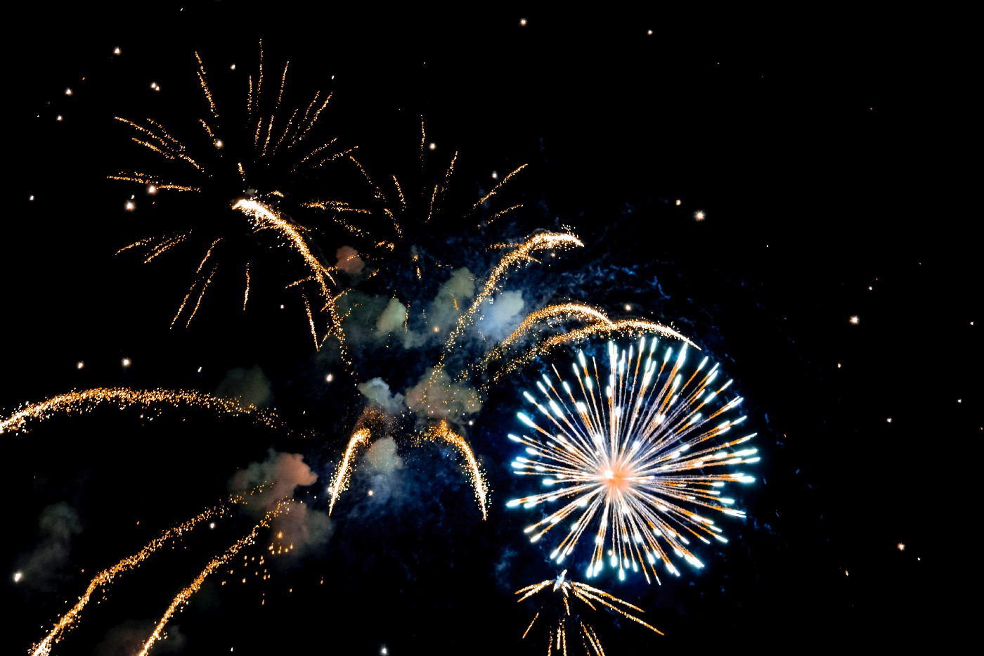 Picture of gold, blue, and white fireworks exploding in the night sky
