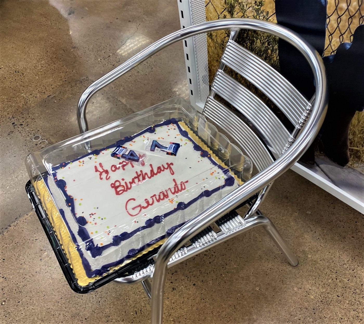 """Picture of white cake with blue trim that reads """"Happy Birthday Gerardo"""" in red icing. The numbers '7' and '4' candles sit atop the lid."""