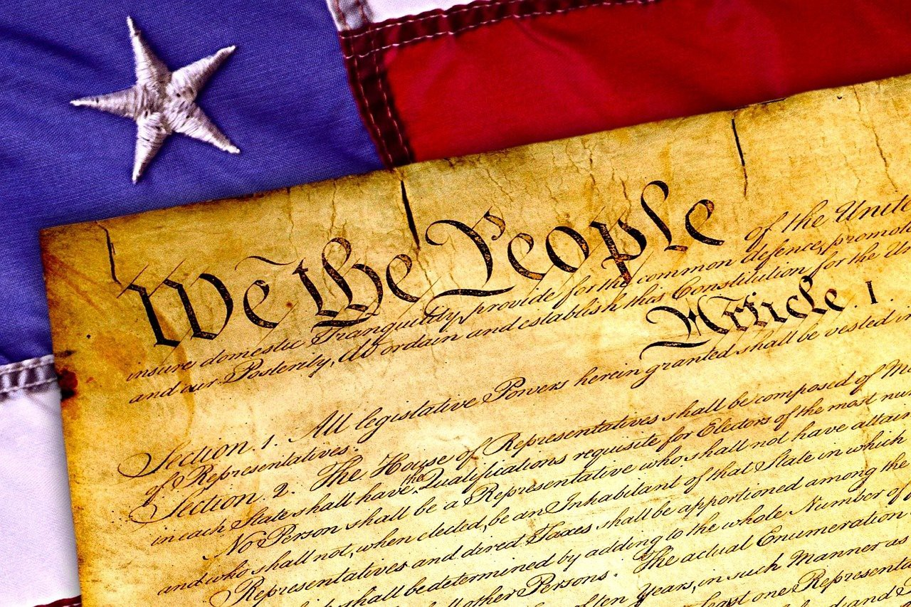 Photo of the heading We the People of the Constitution of the United States of America atop an American flag.