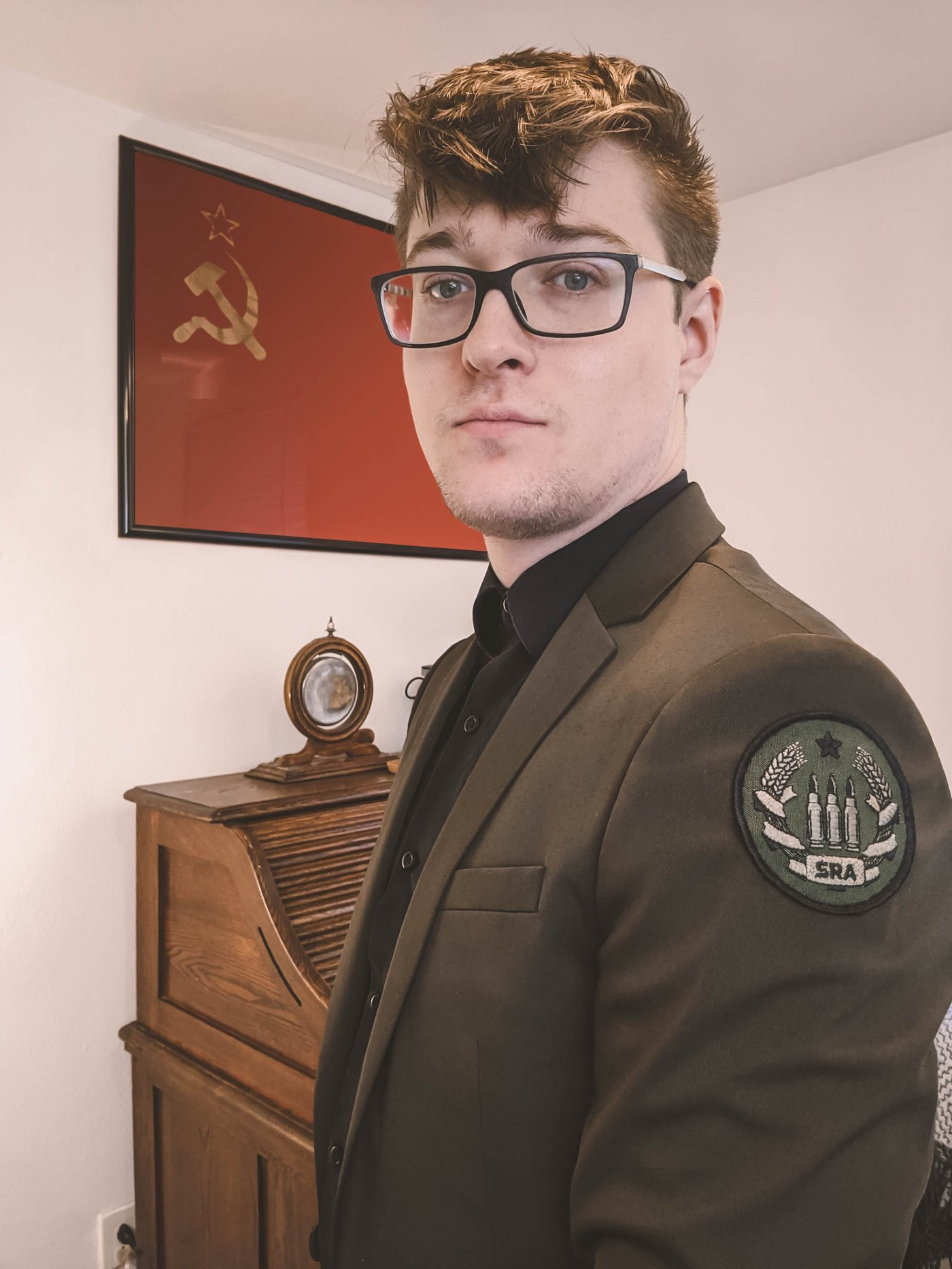 """This photo is of Jason L. Hamilton in an olive green suit (with olive green """"SRA"""" patch) amidst his desk & a Soviet flag."""