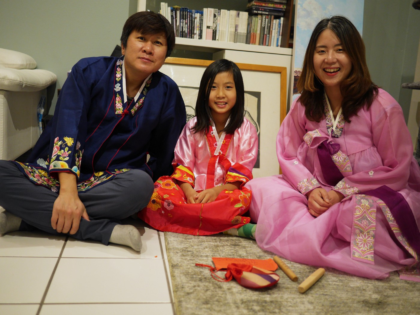 Kyung Hyun Kim sits with his daughter, Sidd Kim, and wife, Yourim Lee, wearing hanbok